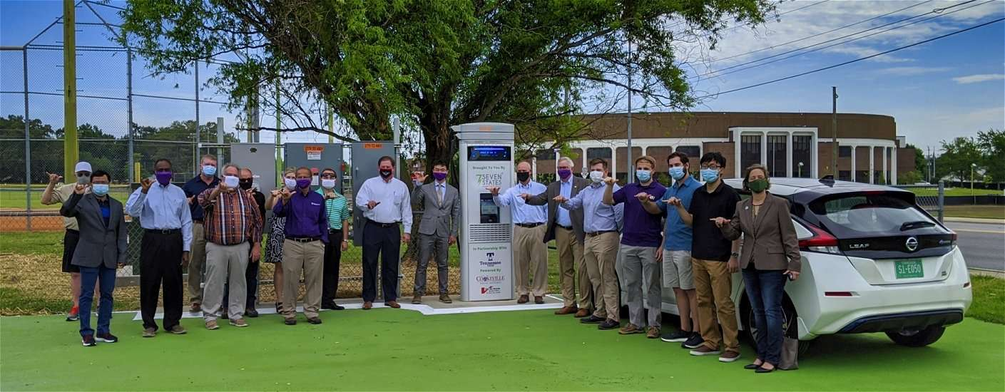 TN Tech DC Fast Charge unit with people standing in front of Nissan Leaf
