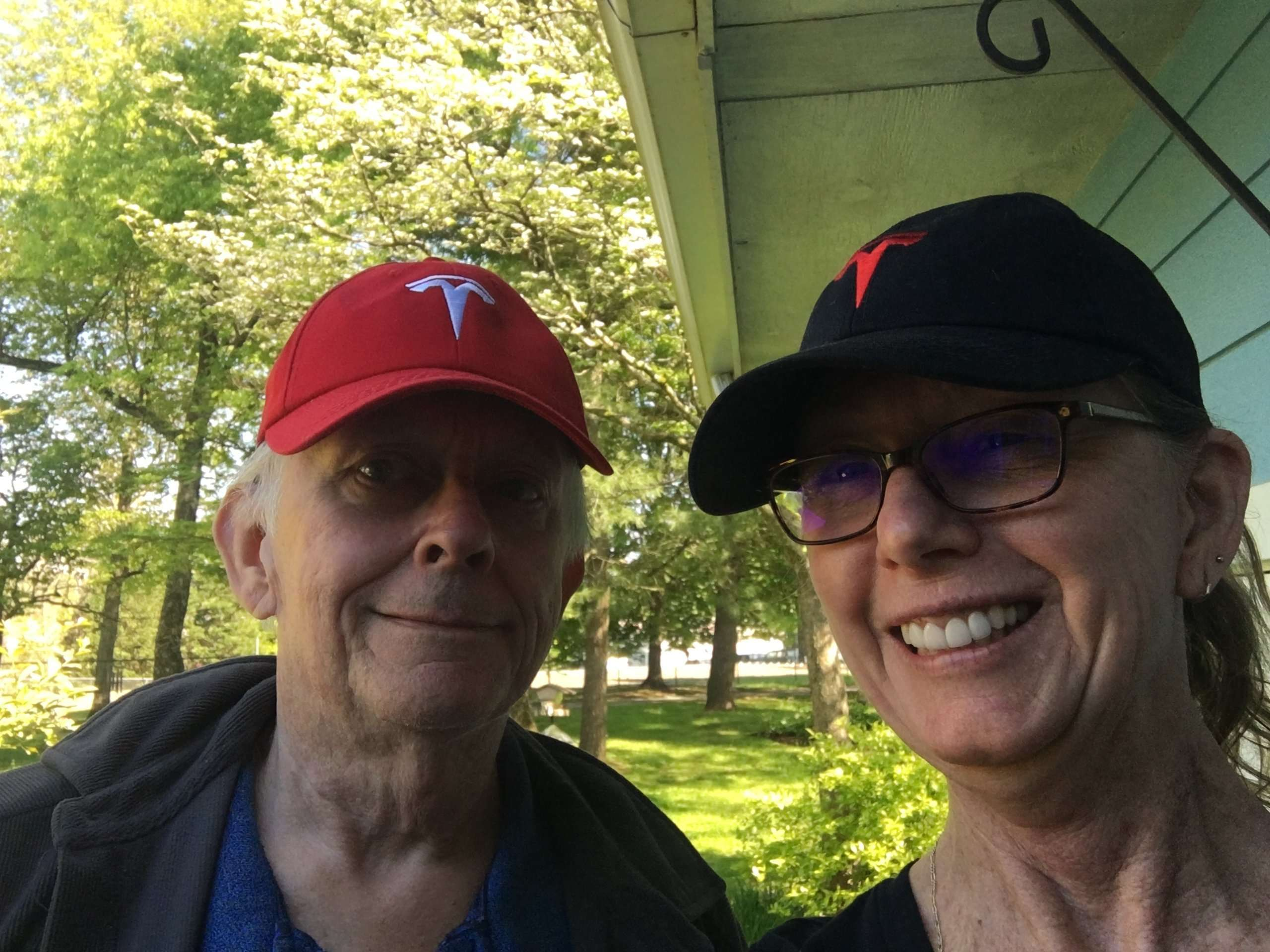 Jack Goodwin stands to the left in a red Tesla hat and Susan Goodwin stand to right in a black Tesla hat taking a selfie.