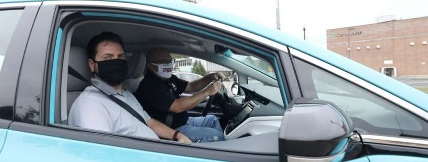 Two men riding in an electric vehicle