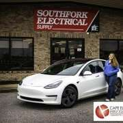 """Woman in blue jacket stands next to her Tesla electric vehicle parked in front of a brick building with a red sign reading, """"Southfork Electrical Supply""""."""