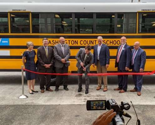 Seven people stand behind red ribbon and in front of yellow, Washington County Schools electric school bus. One man, Jarrod Adams, cuts the ribbon with giant scissors.