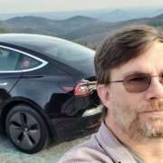 Robert Lipe takes a selfie with his black, Tesla Model 3 behind him and mountains in the background.
