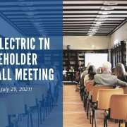 """A group of people sit in a small auditorium for a meeting. On top of a blue background, white text says, """"Drive Electric TN Stakeholder Town Hall Meeting. Join us, July 29, 2021!"""""""