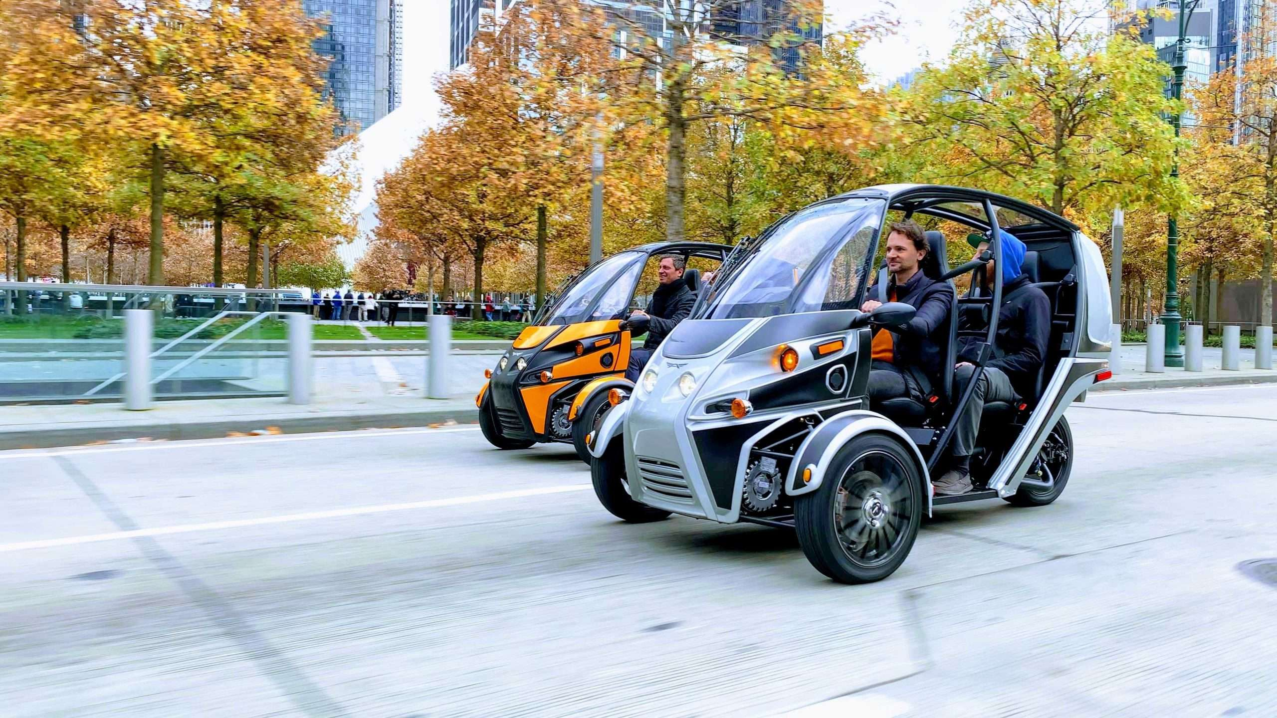 """Two Arcimoto brand, """"Fun Utility Vehicles"""" drive side by side on pavement. The vehicles are three wheeled, have a roof and windshield, but no side doors."""