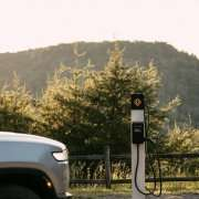 A Rivian brand Level 2 electric vehicle charging station is set up in a park in front of a fence with trees and mountains in the background. A silver car is pulling up from the left side of the photo.