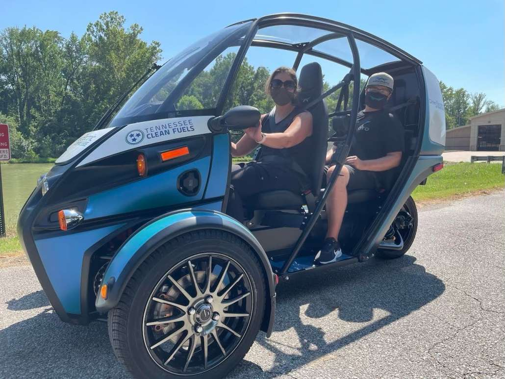 Two people, one driving in the front and one riding in the back, experience a three-wheeled, blue, Arcimoto electric vehicle.
