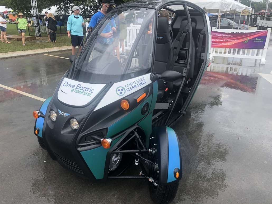 A three-wheeled electric vehicle is parked outside of the Get Off the Grid Festival in a parking lot. The vehicle is blue and green to match the Drive Electric TN logo.