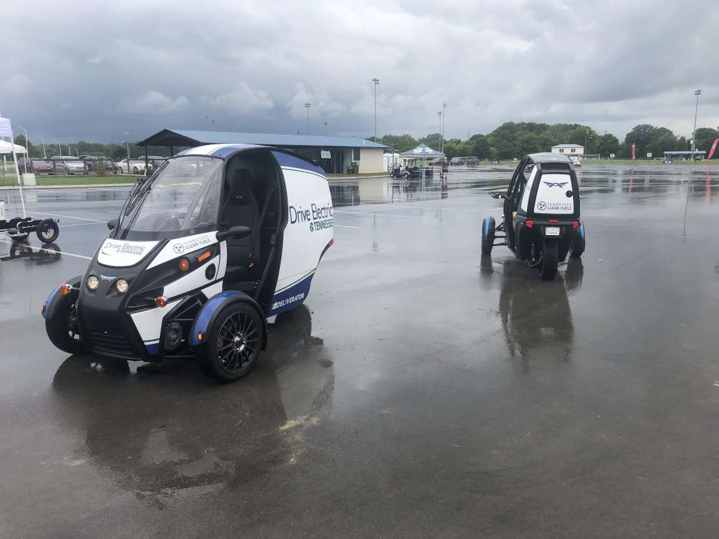 One three-wheeled, electric vehicle with no front doors faces the camera while another drives away to the side. The sky is dark due to rain.
