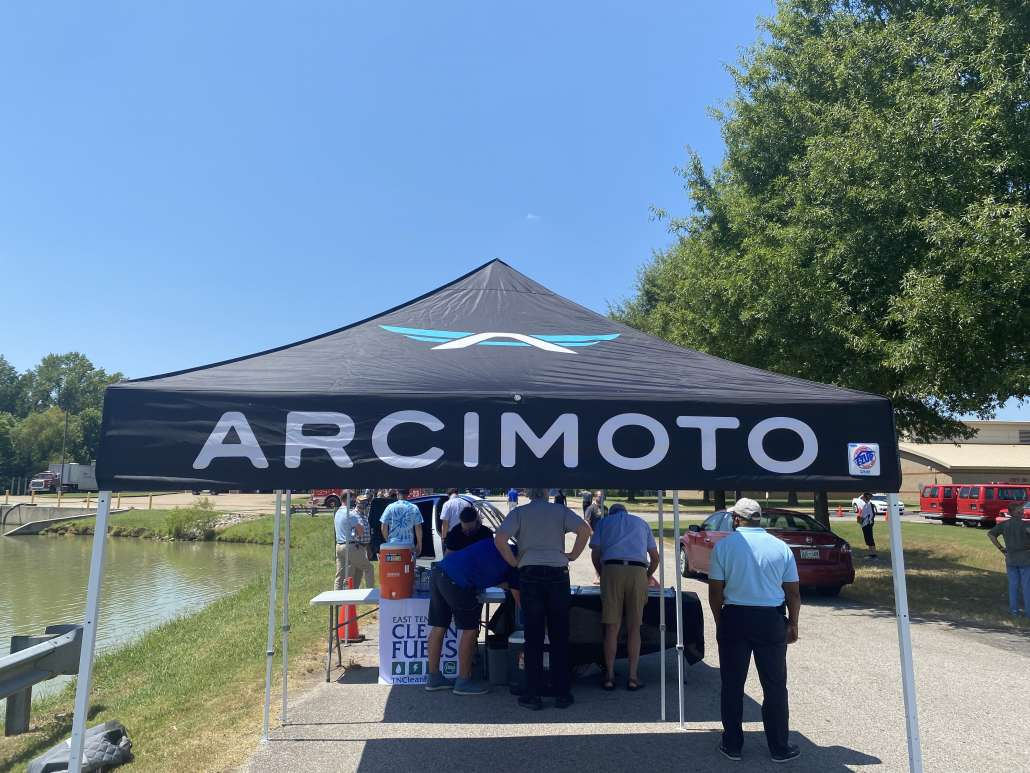 Pop up tent outside next to a pond. The tent is branded with the Arcimoto name and logo. People stand around a table talking.