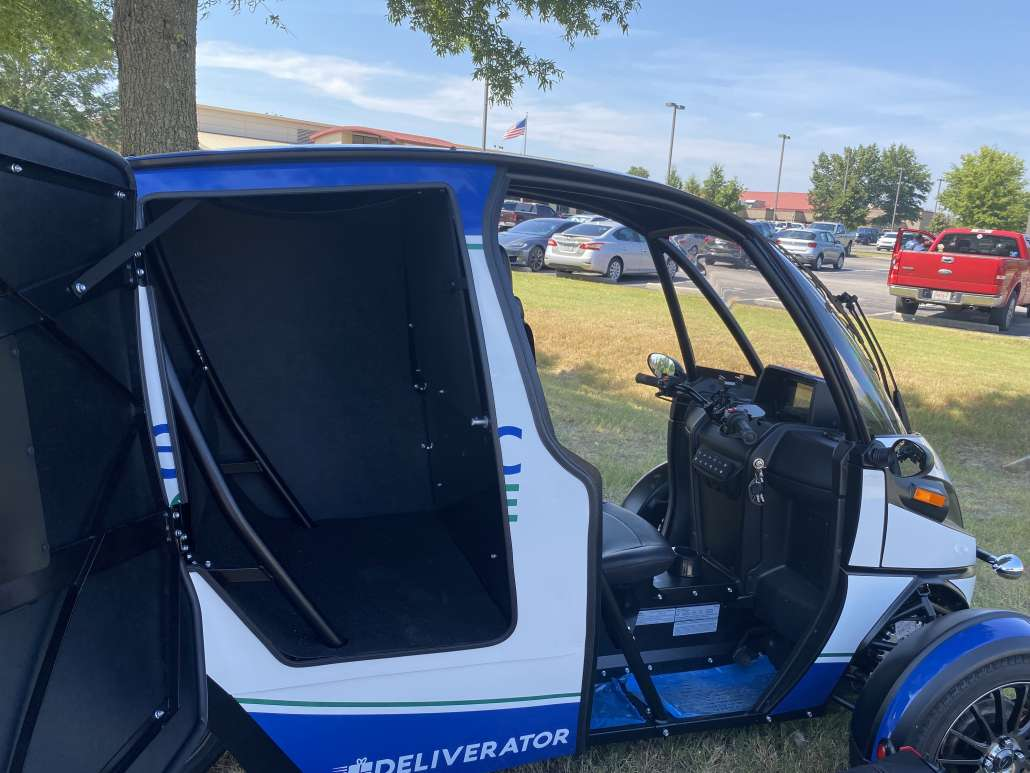 """The Arcimoto, three-wheeled, electric vehicle shows off its profile to see inside the back space on the """"Deliverator"""" vehicle."""