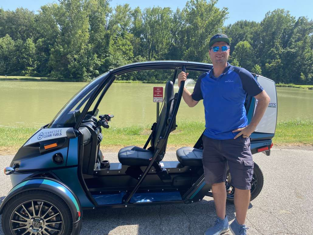 Arcimoto Director of Communications poses in front of the three-wheeled, electric vehicle.