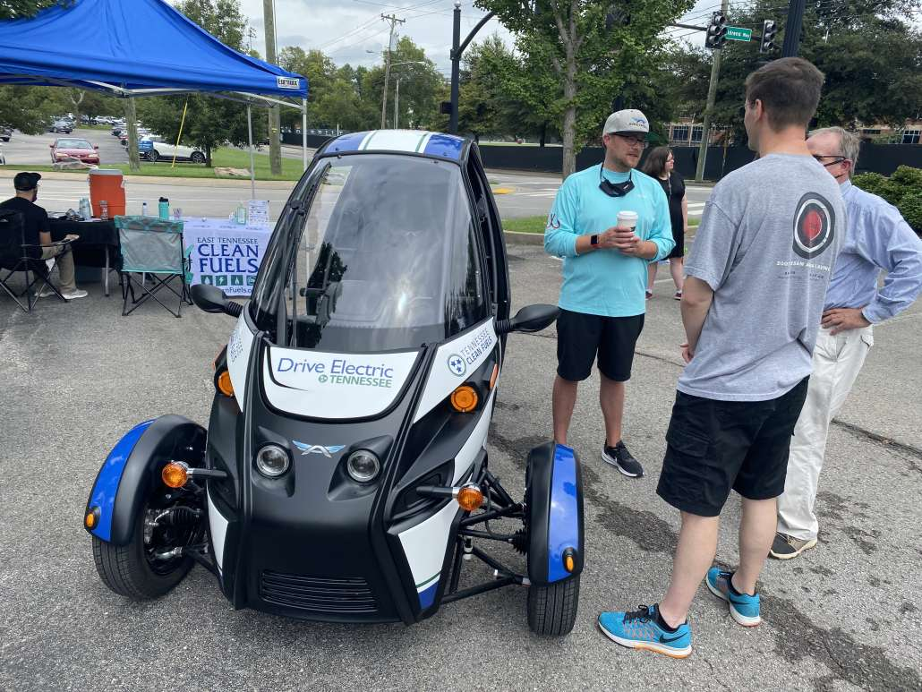Three people stand to the right of the three-wheeled, Arcimoto electric vehicle. A blue tent with tables and a Tennessee Clean Fuels table cloth sit in the back.