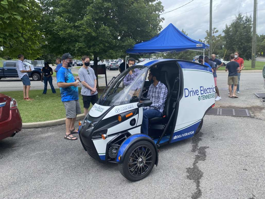 A person sits in the driver seat of an Arcimoto, three-wheeled electric vehicle. People stand to the side talking about the vehicle in a parking lot.