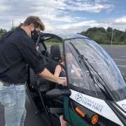 One person in a black shirt and mask stands outside an Arcimoto electric vehicle (no doors) showing another person sitting in the vehicle how to drive it. They are in a parking lot with trees in the background.